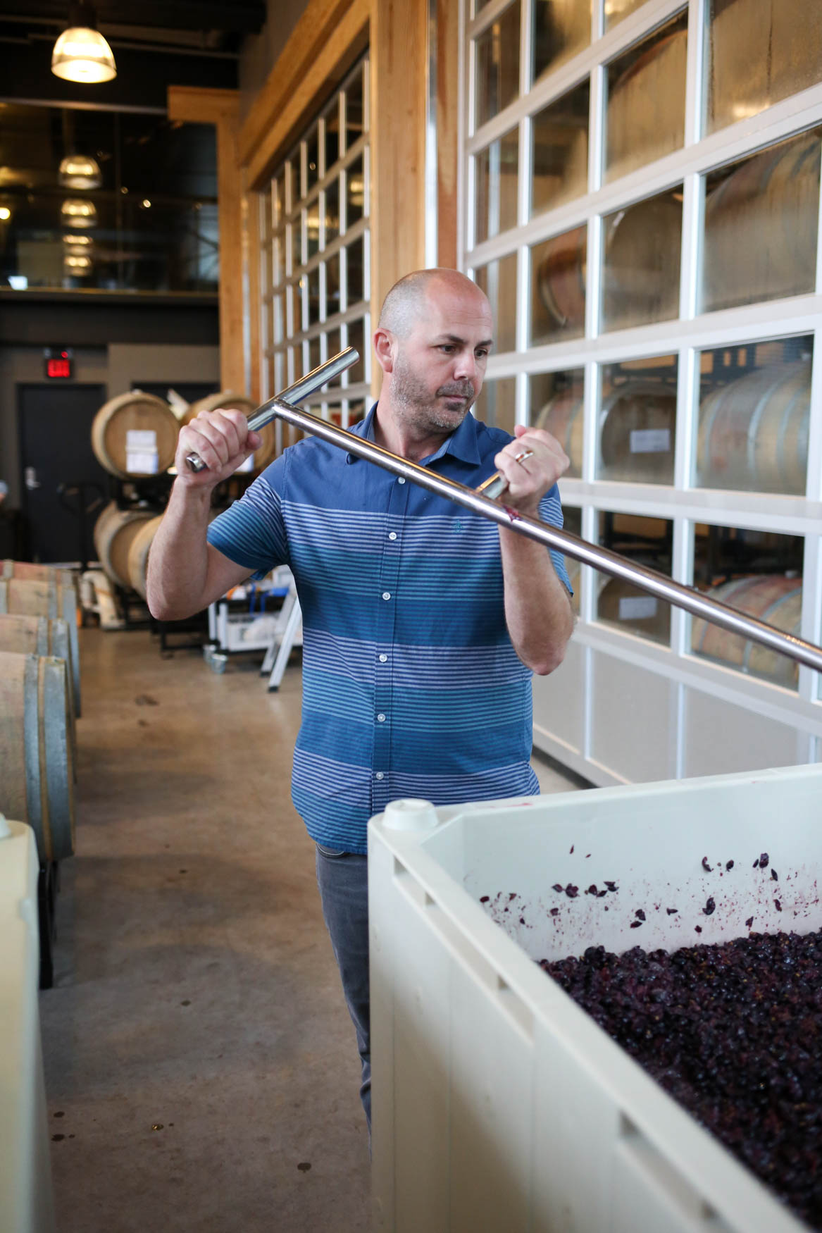 Winemaker Conor McCormack mixes the cap back into the wine.{ }(Amanda Andrade-Rhoades/DC Refined)