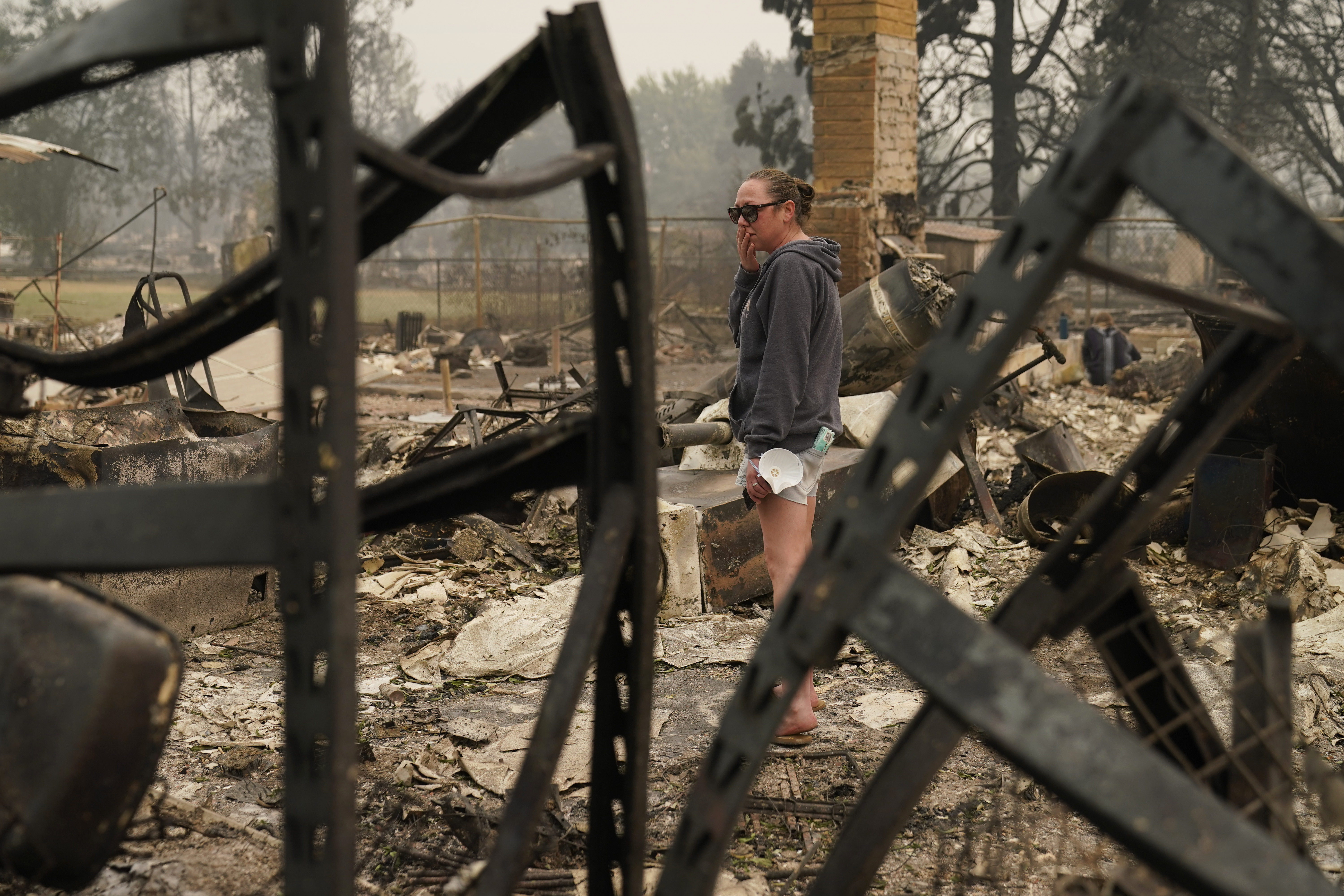"Desiree Pierce reacts as she visits her home destroyed by the Almeda Fire, Friday, Sept. 11, 2020, in Talent, Ore. ""I just needed to see it, to get some closure,"" said Pierce.  (AP Photo/John Locher)"