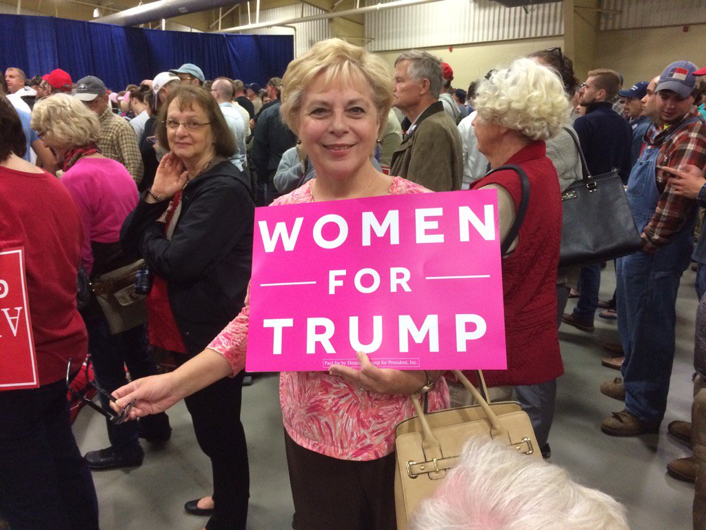 Retired Hickory teacher displays a sign at the Trump rally (Photo credit: WLOS staff)