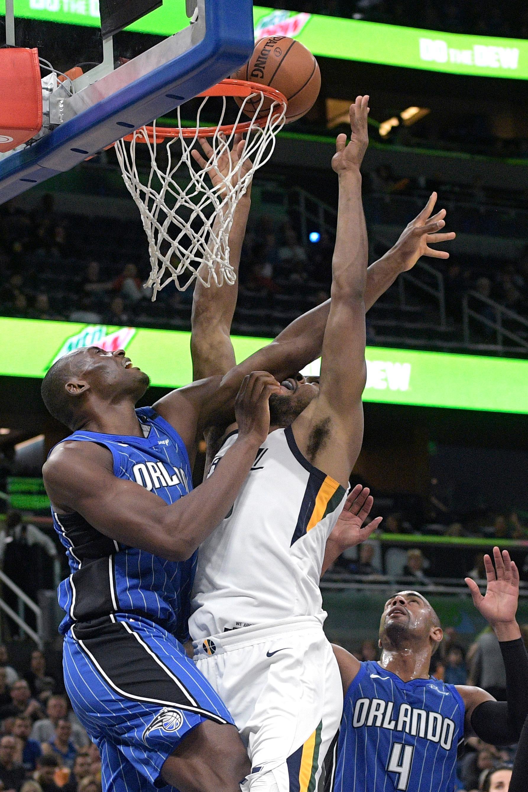 Utah Jazz forward Derrick Favors, center, is fouled by Orlando Magic center Bismack Biyombo (11), left, while going up for a shot as guard Arron Afflalo (4) watches during the second half of an NBA basketball game, Saturday, Nov. 18, 2017, in Orlando, Fla. The Jazz won 125-85. (AP Photo/Phelan M. Ebenhack)