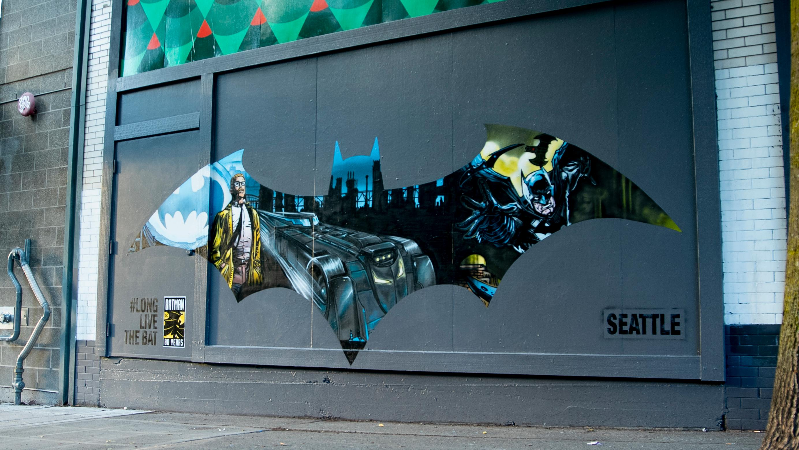 "To celebrate 80 years of Batman, DC is bringing fans a series of murals inspired by ""The World's Greatest Detective"" in four cities across the country, including Seattle! Seattle artist Joey Nix painted Seattle's mural outside of landmark music venue, The Crocodile. You can find the 10-foot painting which will be on display through the end of June (Image courtesy of DC)."