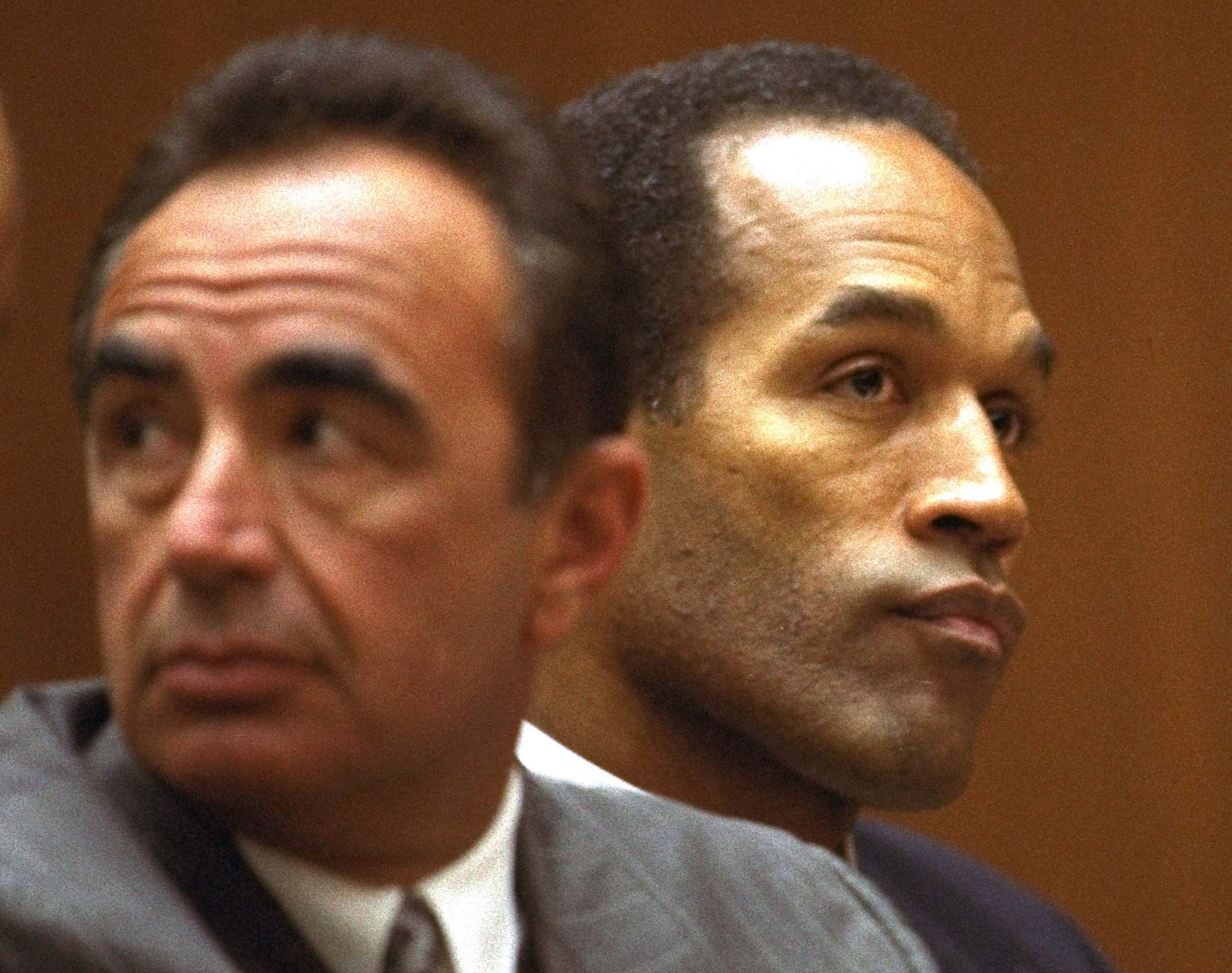 In this Friday, Aug. 26, 1994, file photo, O.J. Simpson and defense attorney Robert Shapiro sit in a Los Angeles Superior courtroom as Judge Lance Ito refused a request to open an afternoon session to the media. NICK UT/THE ASSOCIATED PRESS