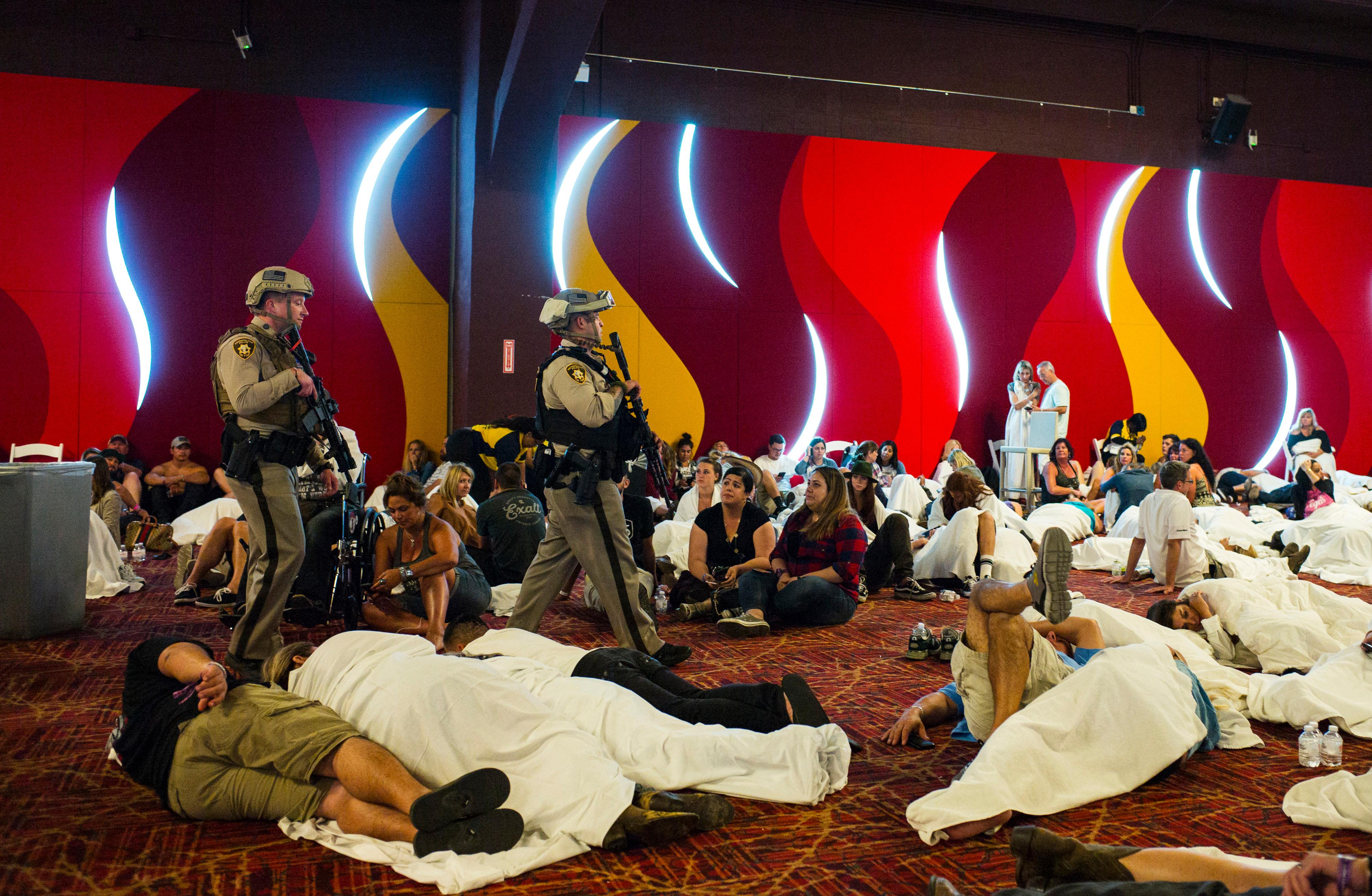 Las Vegas police sweep through a convention center area during a lockdown Monday, Oct. 2, 2017, at the Tropicana Las Vegas following an active shooter situation on the Las Vegas Strip. Multiple victims were transported to hospitals after a deadly shooting late Sunday at a music festival on the Las Vegas Strip. (Chase Stevens/Las Vegas Review-Journal via AP)