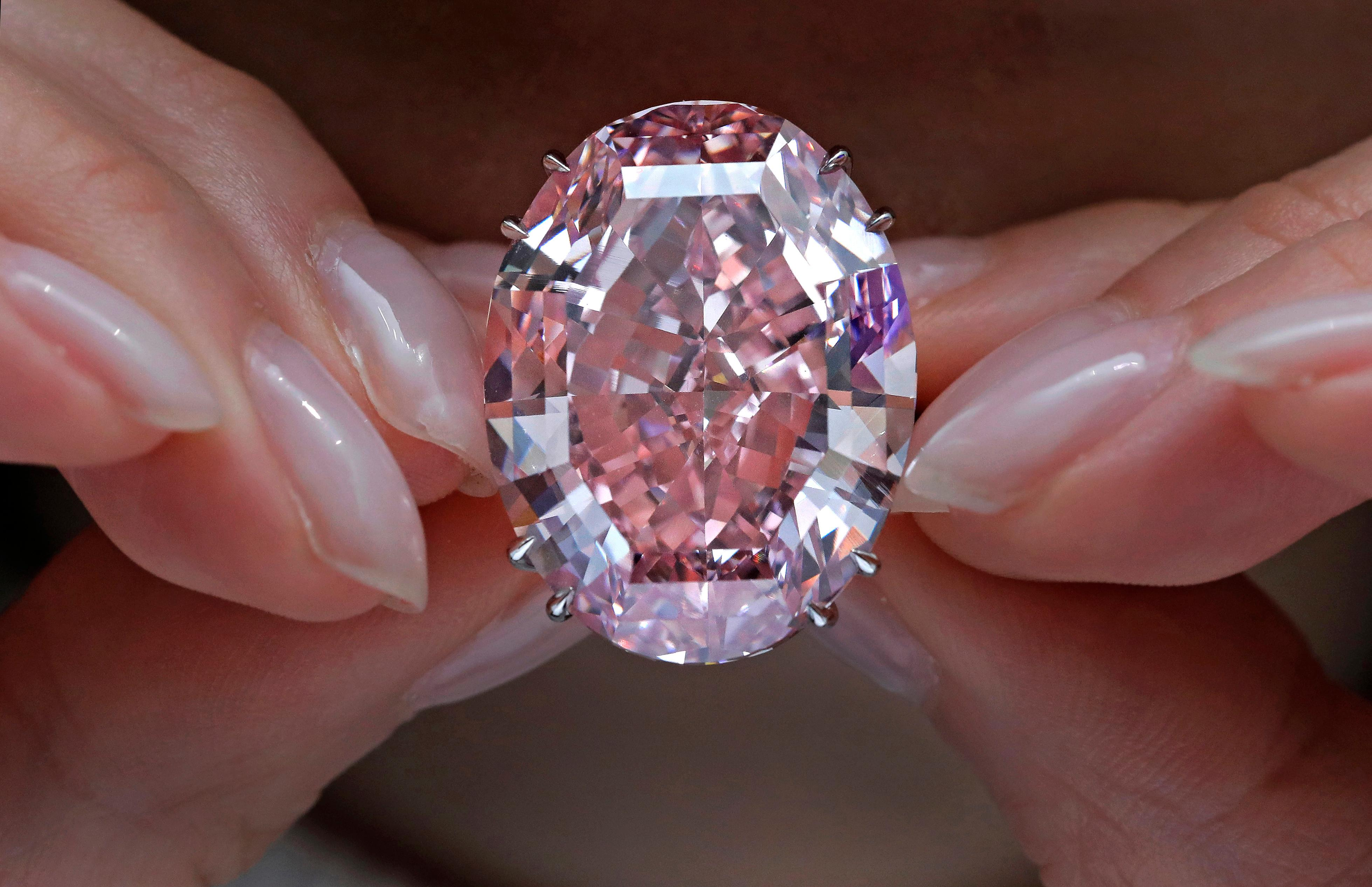 "FILE - In this Wednesday, March 29, 2017, file photo, the ""Pink Star"" diamond, the most valuable cut diamond ever offered at auction, is displayed by a model at a Sotheby's auction room in Hong Kong. (AP Photo/Vincent Yu, File)"