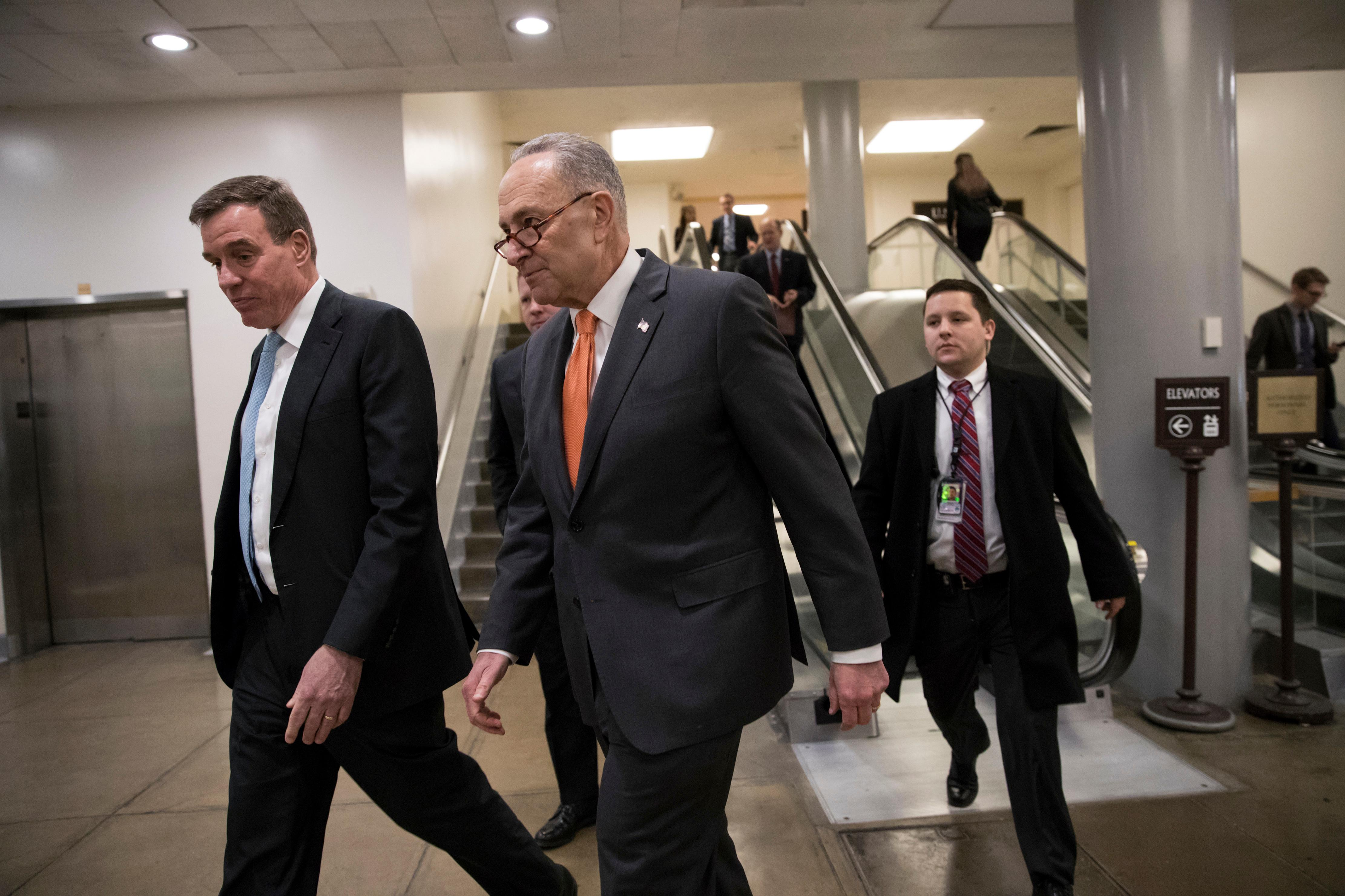 Senate Minority Leader Chuck Schumer, D-N.Y., center, and Sen. Mark Warner, D-Va., left, the vice chair of the Senate Select Committee on Intelligence, head to a closed security briefing at the Capitol in Washington, Tuesday, Feb. 6, 2018. (AP Photo/J. Scott Applewhite)
