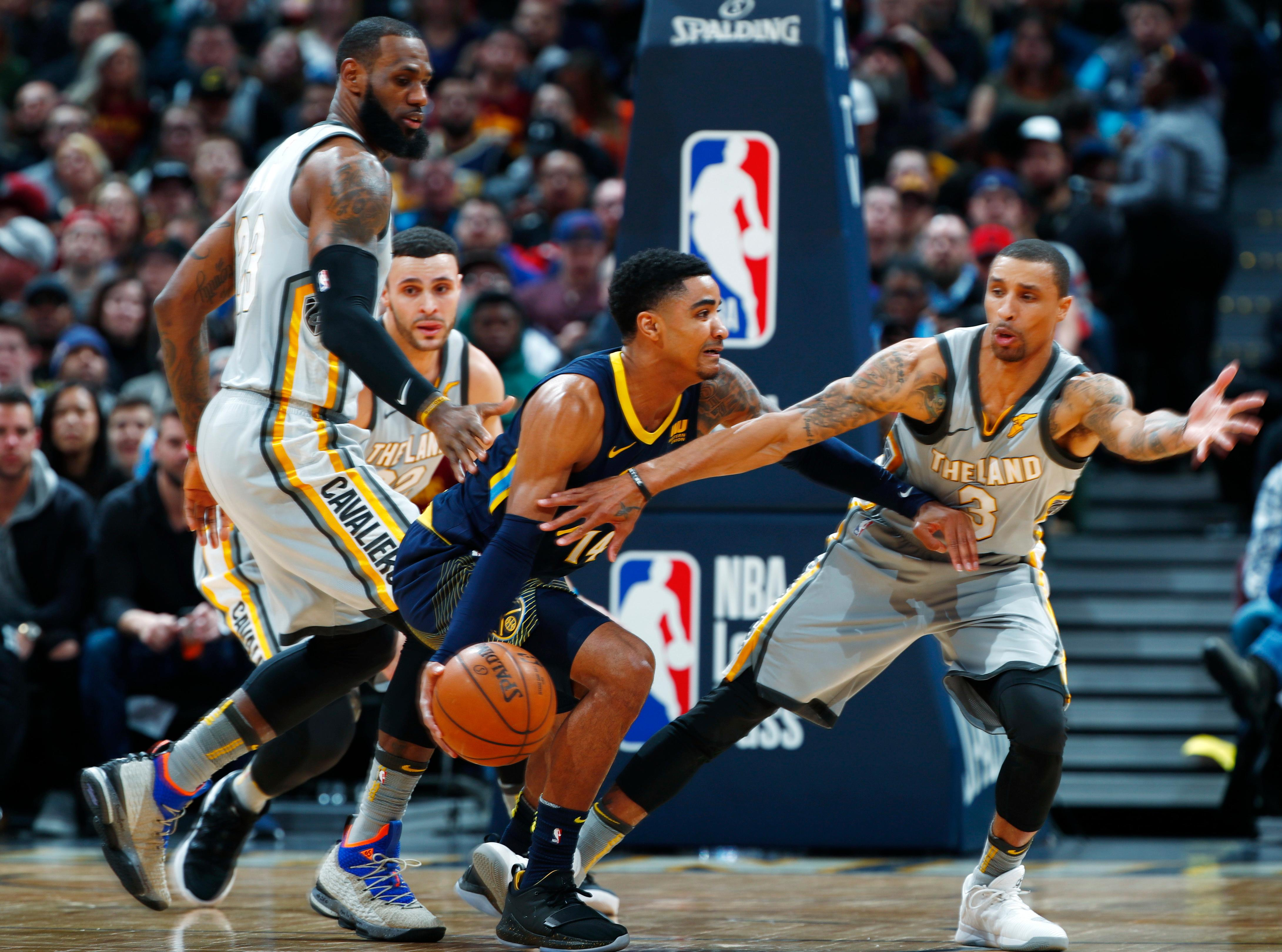 Denver Nuggets guard Gary Harris, center, drives between Cleveland Cavaliers forward LeBron James, left, and guard George Hill during the first half of an NBA basketball game Wednesday, March 7, 2018, in Denver. (AP Photo/David Zalubowski)