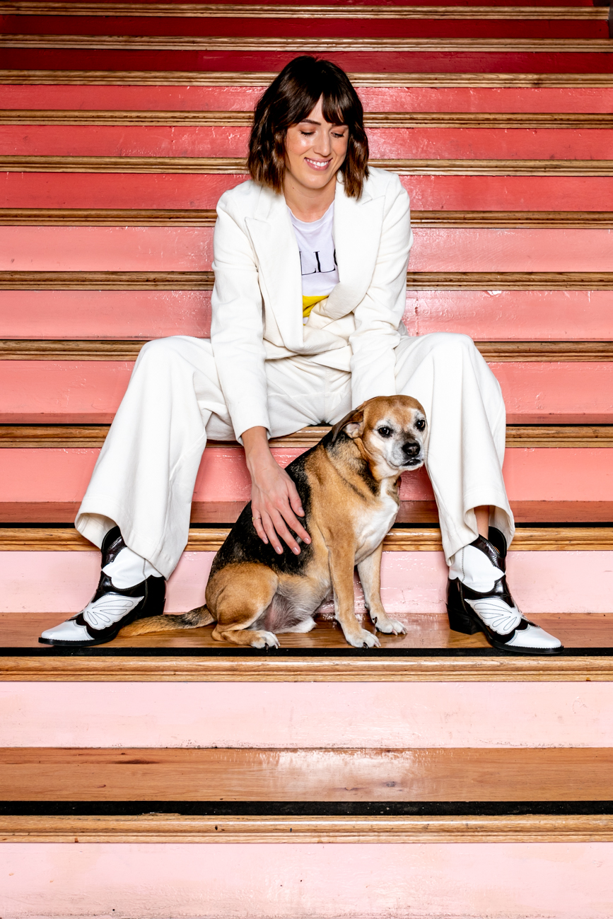 "Laura Hughes and her dog, George Michael, pose for a photograph on some stairs inside Union Hall for her Fashion Spotlight interview. First published on October 17 in ""Laura Hughes: The Stylish Dresser of Vine Street's Union Hall"" / Image: Amy Elisabeth Spasoff"