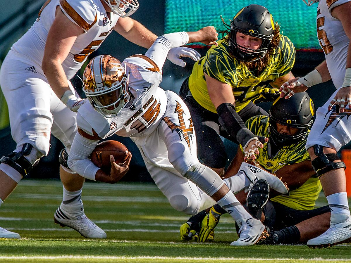 The Sun Devils' Bryson Echols (#15) finds an opening as the Ducks try to bring him down. The Oregon Ducks broke their losing streak by defeating the ASU Sun Devils on Saturday 54-35. Photo by August Frank, Oregon News Lab