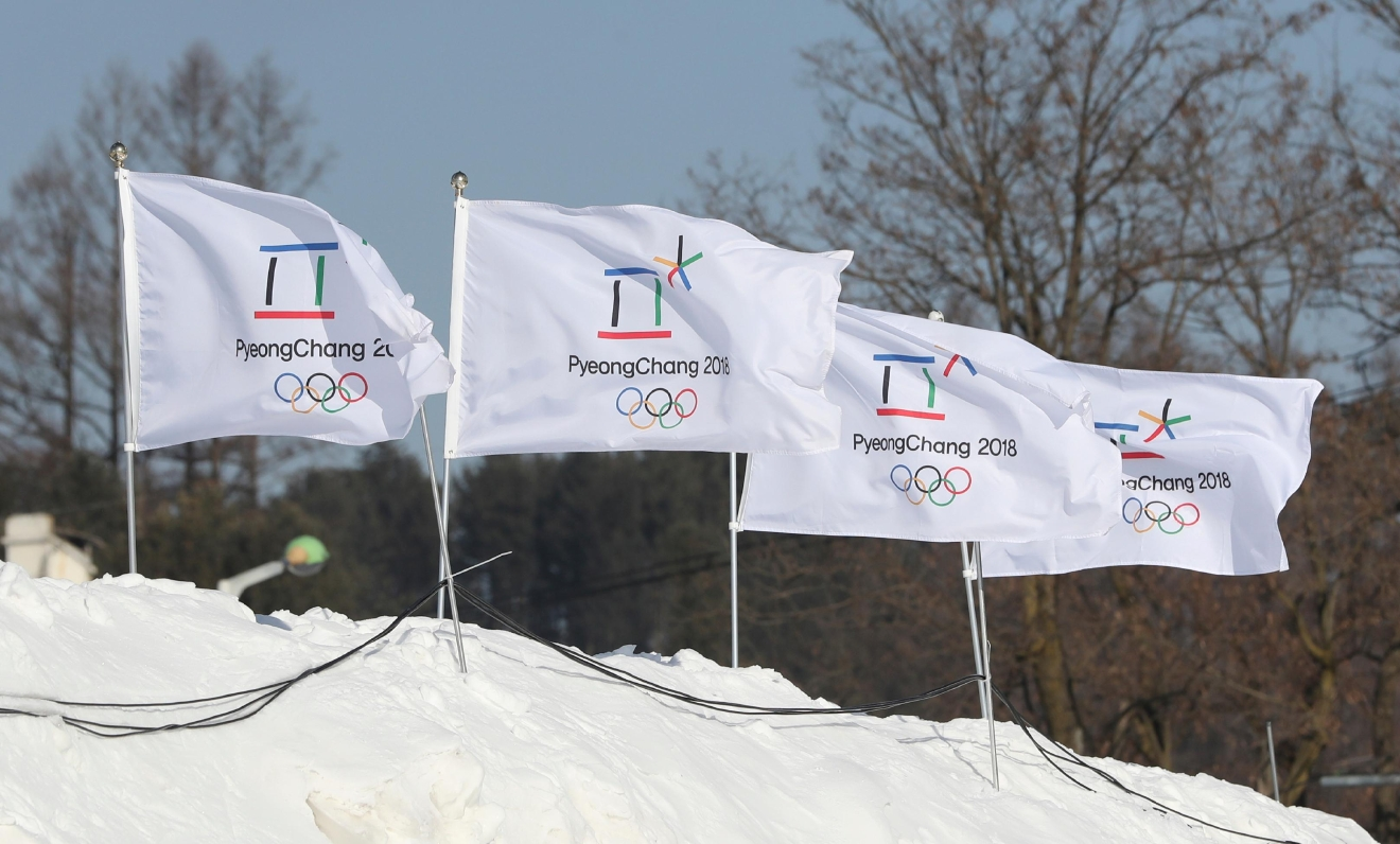 In this Friday, Feb. 3, 2017 photo, flags with the emblem of the 2018 Pyeongchang Olympic Winter Games flutter in Pyeongchang, South Korea. One year before the Olympics, the country is in political disarray, and winter sports are the last thing on many people's minds. To say that South Koreans are distracted from what had been billed as a crowning sports achievement is an understatement. (AP Photo/Lee Jin-man)