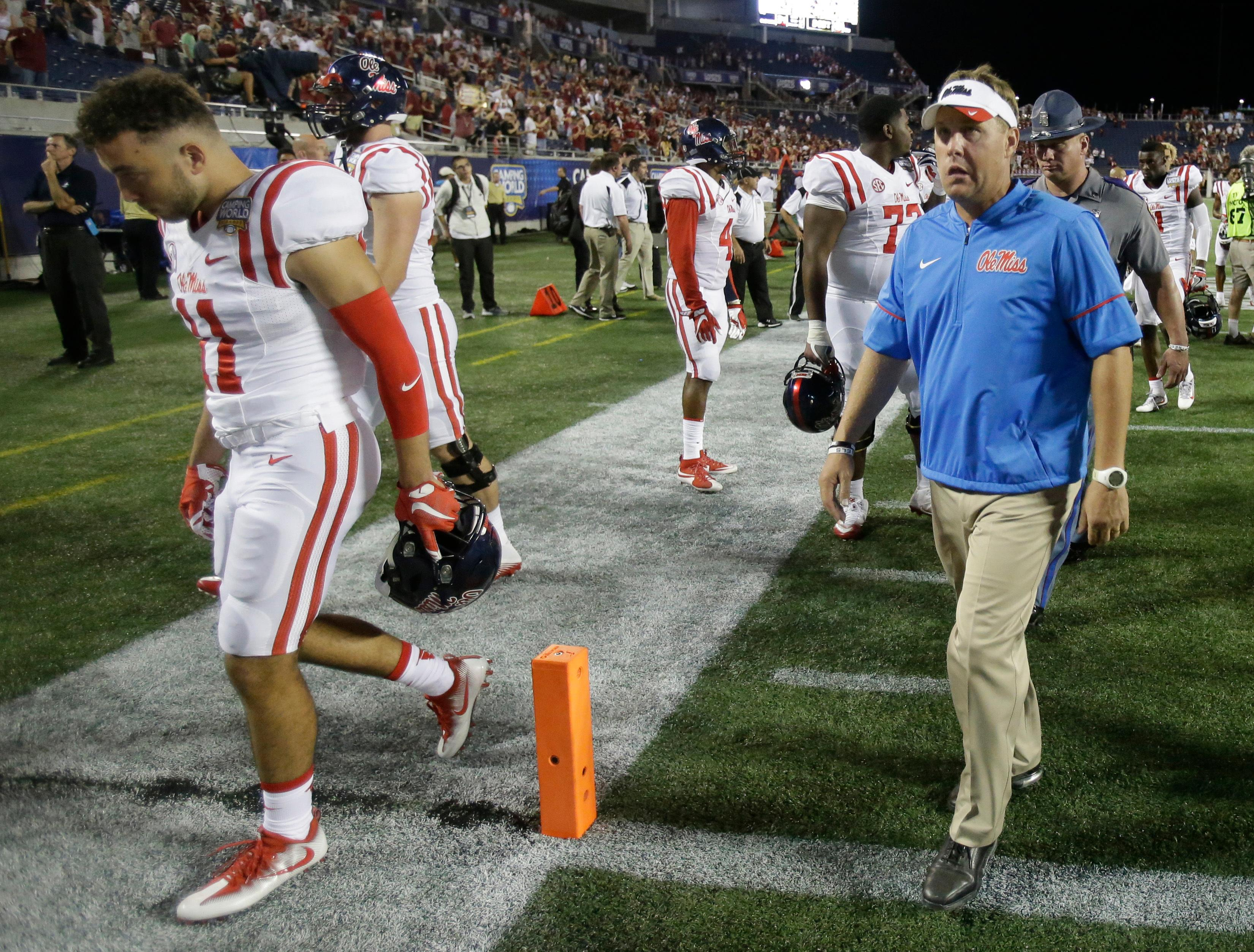 FILE - In this Sept. 5, 2016, file photo, Mississippi coach Hugh Freeze, right, leaves the field with players after their 45-34 loss to Florida State in an NCAA college football game in Orlando, Fla. Freeze has resigned after five seasons, bringing a stunning end to a once-promising tenure.                  The school confirmed Freeze's resignation in a release Thursday night. Assistant Matt Luke has been named the interim coach. (AP Photo/John Raoux, File)