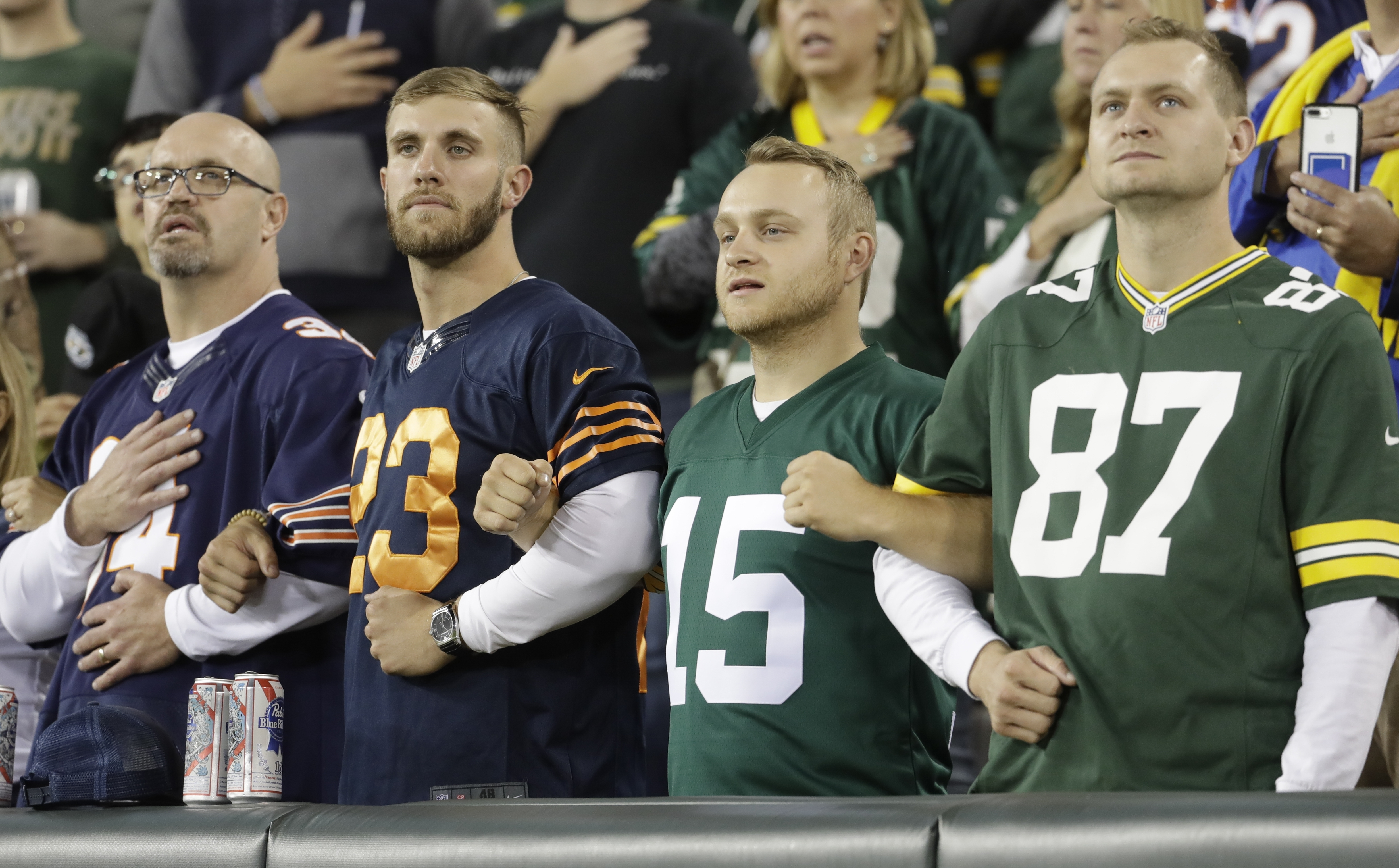 Fans lock arms during the national anthem before an NFL football game between the Green Bay Packers and the Chicago Bears Thursday, Sept. 28, 2017, in Green Bay, Wis. (AP Photo/Morry Gash)