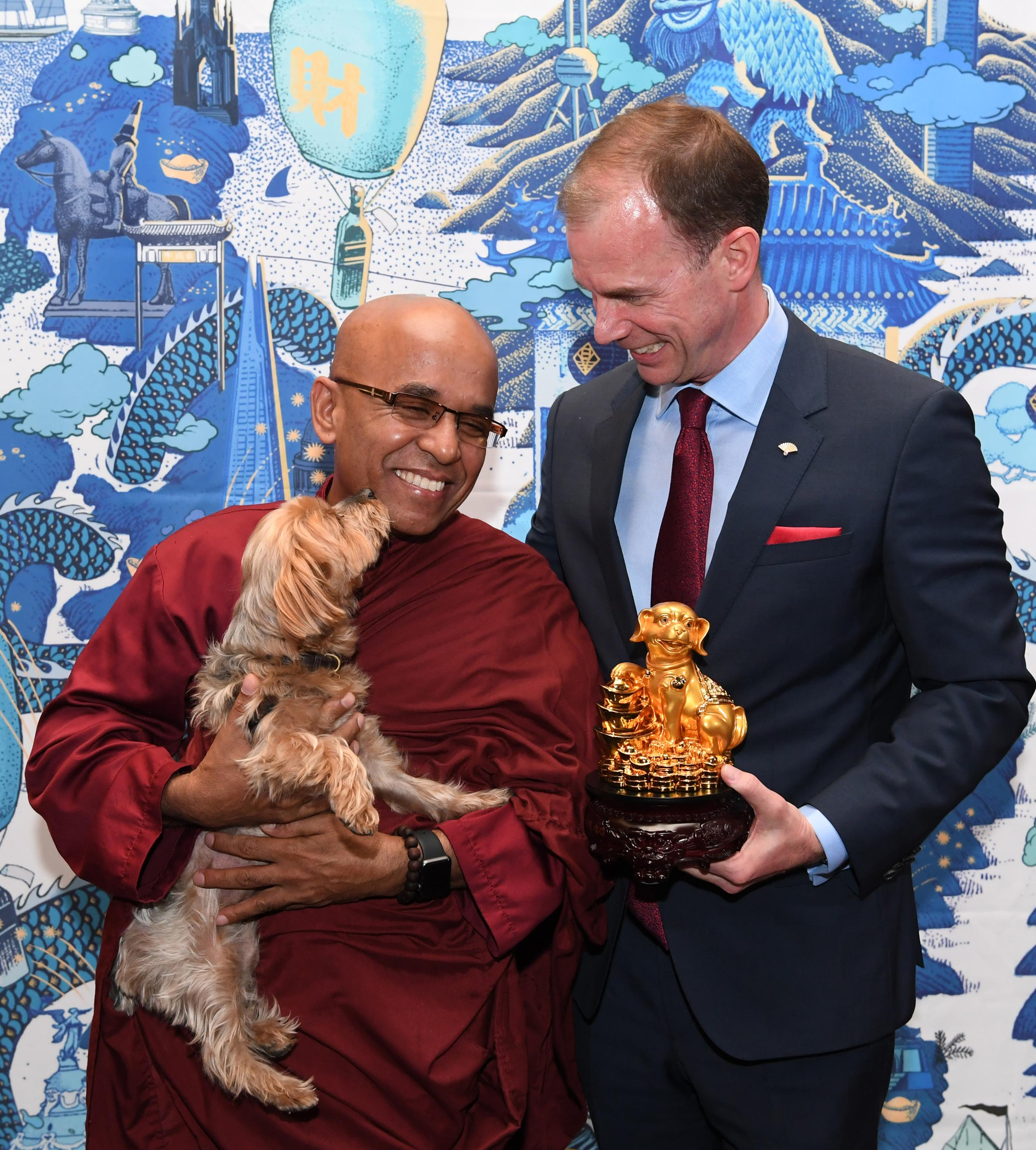 Bhante Sujatha of the Blue Lotus Buddhist Temple gets a kiss from DJ the dog while his owner Donald Bowman, General Manager Mandarin Oriental looks on as the Mandarin Oriental, Las Vegas celebrates the Chinese New Year, Year of the Dog with a special Yusheng Toss presentation. Thursday, February 15, 2018. CREDIT: Glenn Pinkerton/Las Vegas News Bureau