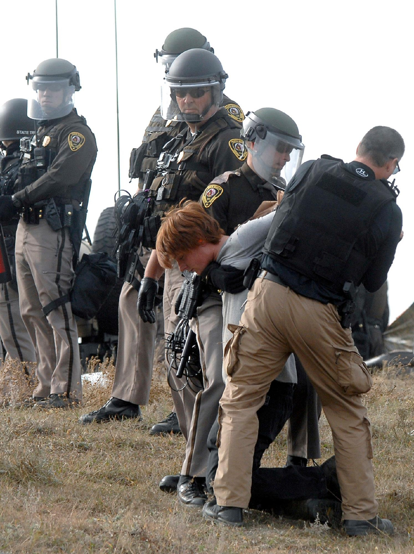 An unidentified Dakota Access Pipeline protester is arrested inside the Front Line Camp as law enforcement surround the camp to remove the protesters from the property and relocated to the overflow camp a few miles south of Highway 1806 in Morton County, N.D., Thursday, Oct. 27, 2016. (Mike McCleary/The Bismarck Tribune via AP)
