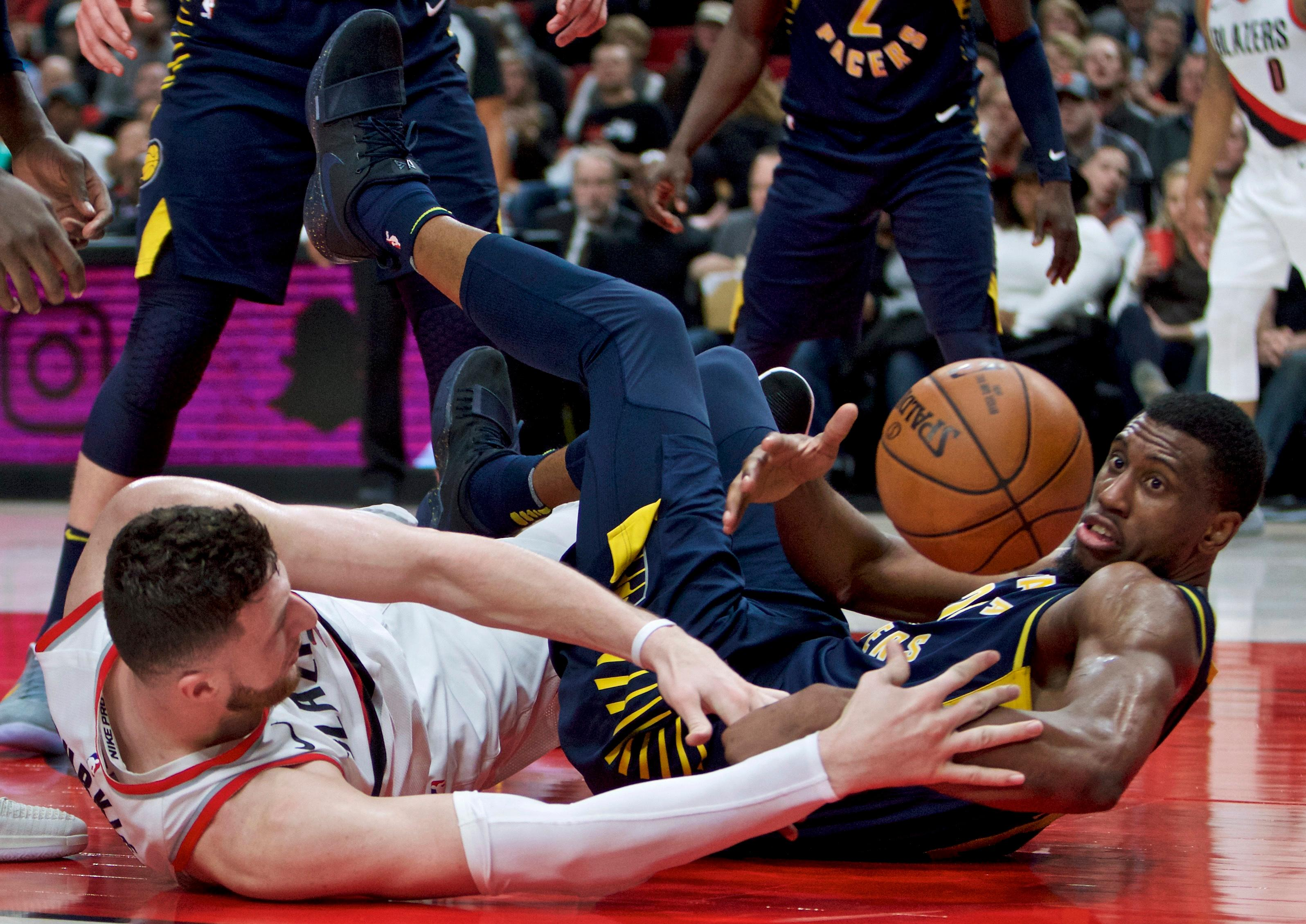 Indiana Pacers forward Thaddeus Young, right, and Portland Trail Blazers center Jusuf Nurkic reach for a loose ball during the second half of an NBA basketball game in Portland, Ore., Thursday, Jan. 18, 2018. (AP Photo/Craig Mitchelldyer)