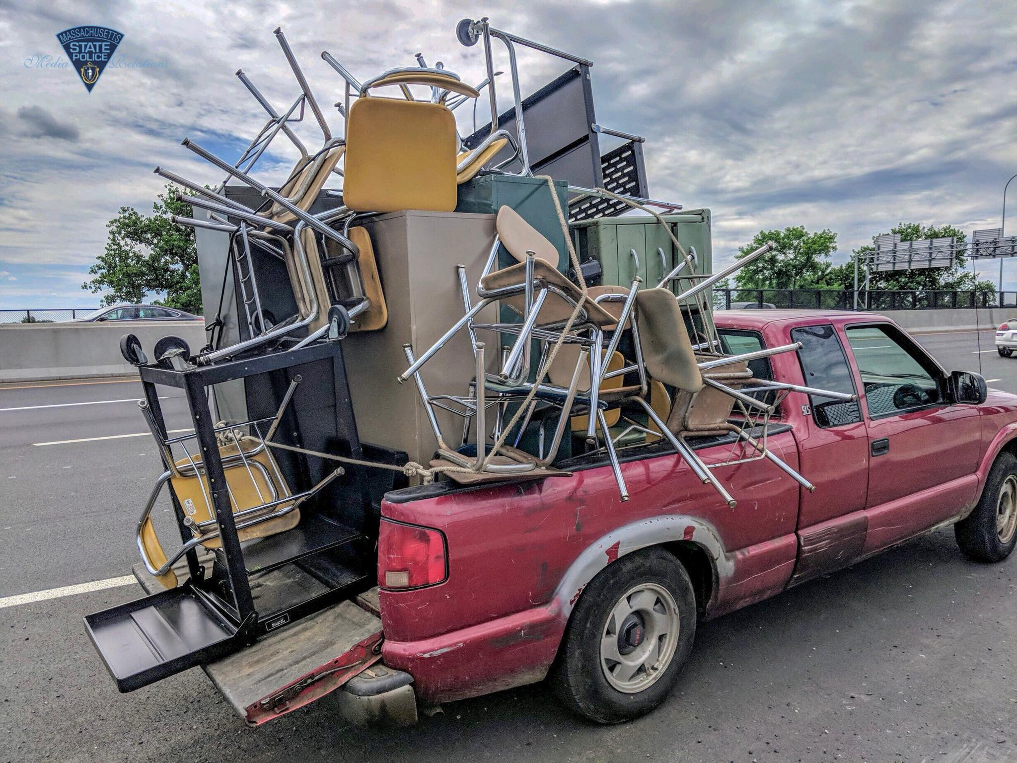 Massachusetts State Police released this image of a pickup truck piled with office furniture on Interstate 91 in Springfield.{ }