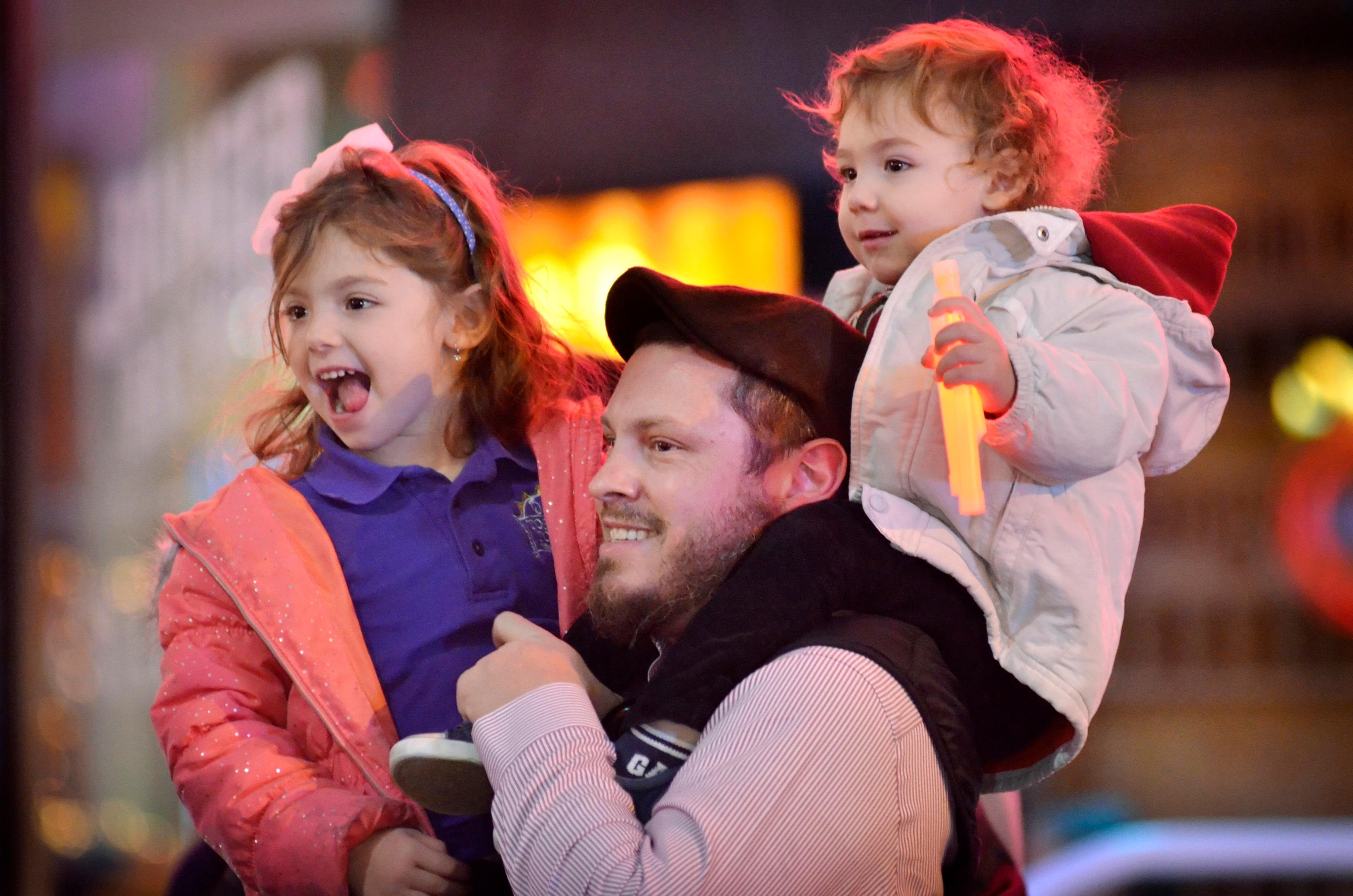 Mordechai Bogatin, center watches a menorah lighting ceremony with his daughter Rivky, left, and son Noach. Rabbi Shea Harlig, of the Chabad Jewish Center of Southern Nevada, Las Vegas Mayor Carolyn Goodman, Jonathan Jossel, CEO of the Plaza hotel-casino, and Patrick Hughes, President and CEO of Fremont Street Experience, were on hand for the first night of Hanukkah which was marked with the lighting of a 20-foot Grand Menorah on Fremont Street in downtown Las Vegas on Tuesday, Dec. 12, 2017. CREDIT: Bill Hughes/Las Vegas News Bureau